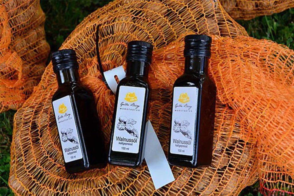 Drei dunkle Glasflaschen mit Walnussöl auf einem Scak voller Walnüsse.