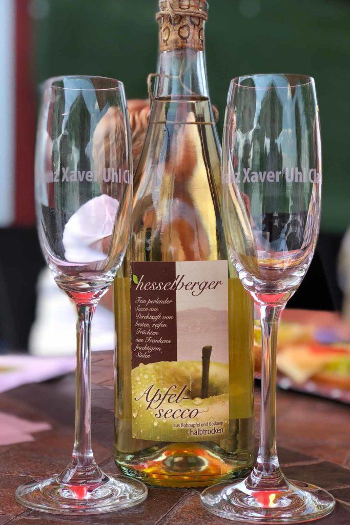 Eine Glasflasche mit Obstsekt und zwei leere Gläser stehen auf einem Tisch.