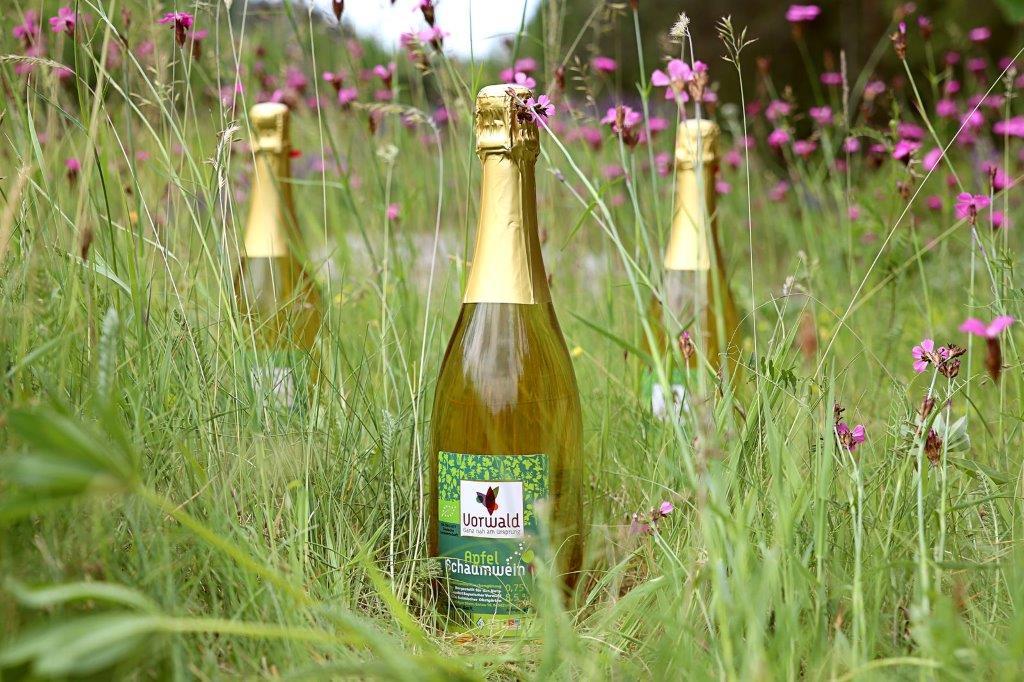 Drei Schaumweinflaschen mit grünem Etikett stehen in einer Blumenwiese.