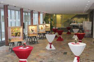 In einem festlich geschmückten Raum ist die Ausstellung aufgebaut.