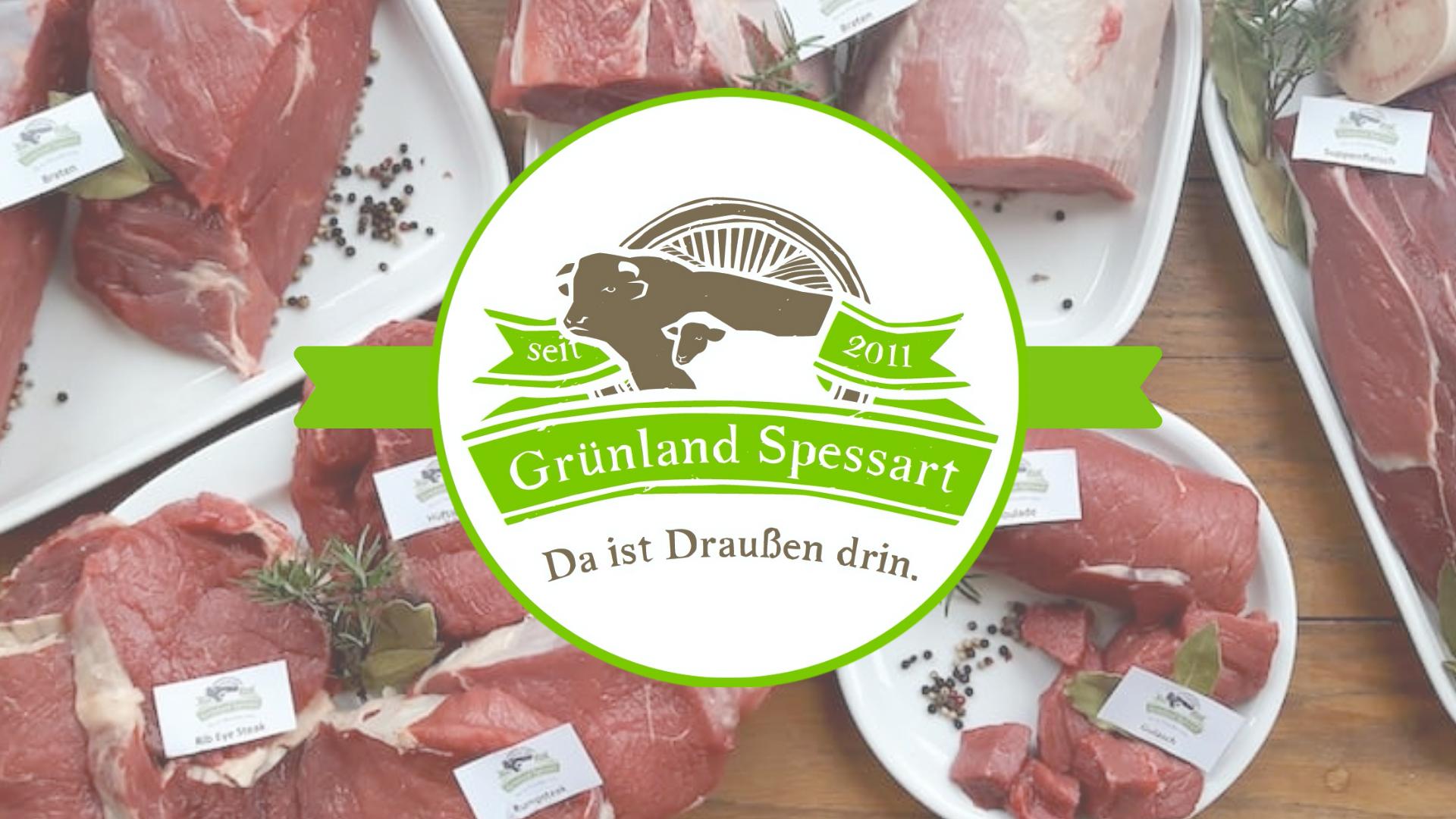 Verschiedene rohe Fleischstücke auf Tellern angerichtet darüber das Logo von Grünland Spessart.