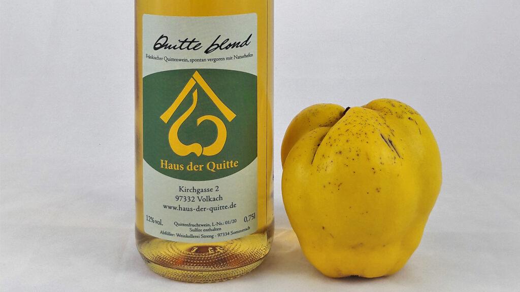 Eine Flasche Quittenwein blond, daneben eine reife, gelbe Quitte