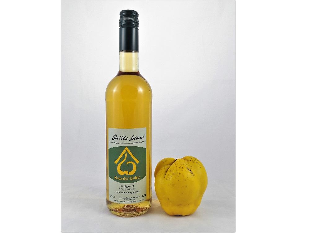 Goldgelber Quittenwein in einer Galsflasche, rechts im Bild eine reife Quitte.