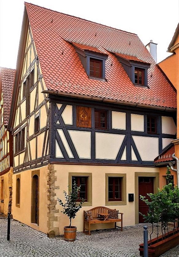 Ein altes Fachwerkhaus mit rotem Ziegeldach in einer mit Kopfsteinen gepflasterten Gasse.