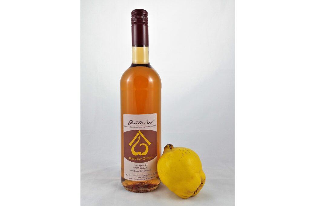 Bernsteinfarbener Quittenwein in einer Galsflasche, an der eine reife gelbe Quitte lehnt.