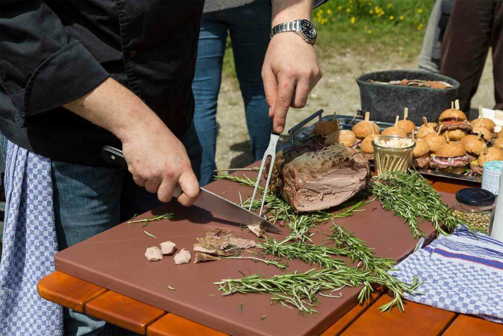 Lammbraten wird auf einem Schneidebrett mit einem großen Messer in kleine Stücke geschnitten, daneben liegen Kräuter.