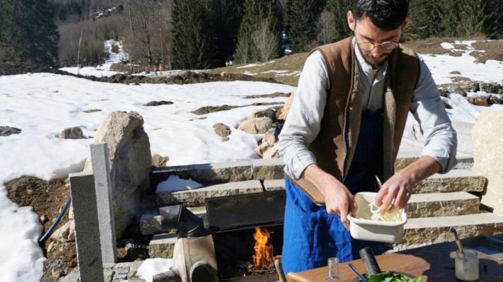 Max Müller kocht in einer improvisierten Outdoor-Küche. Im Hintergrund sieht man die Berge.