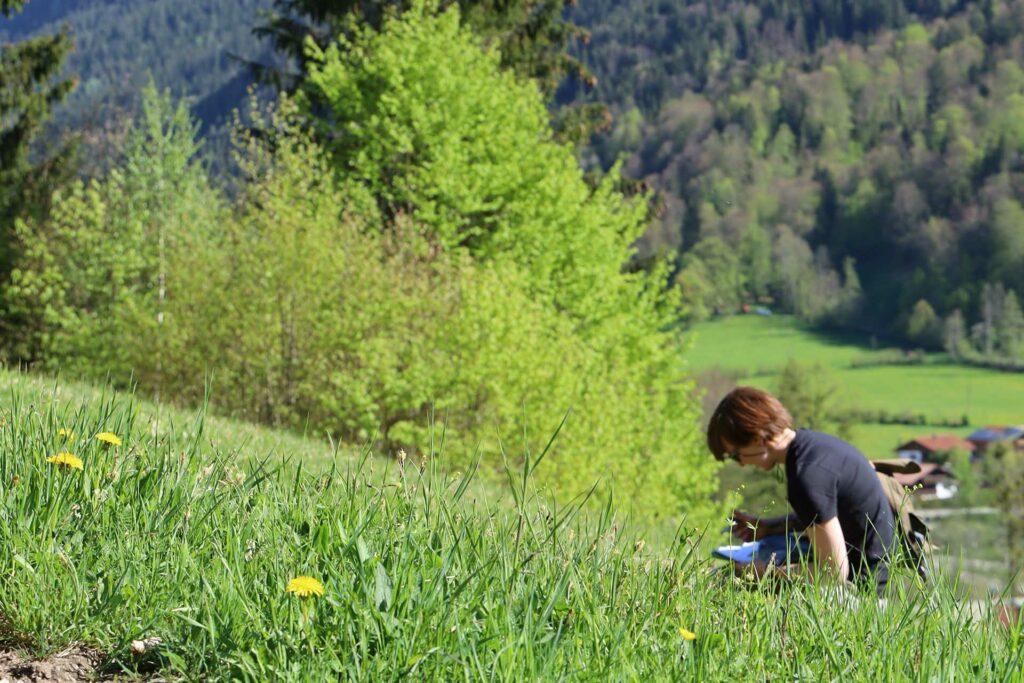 Auf einer frühlingsgrünen Wiese such eine rothaarige FRau nach Schlüsselblumen.