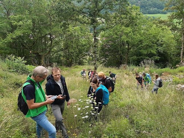 Eine Exkursionsgruppe steht auf einer Hangwiese und betrachtet Pflanzen