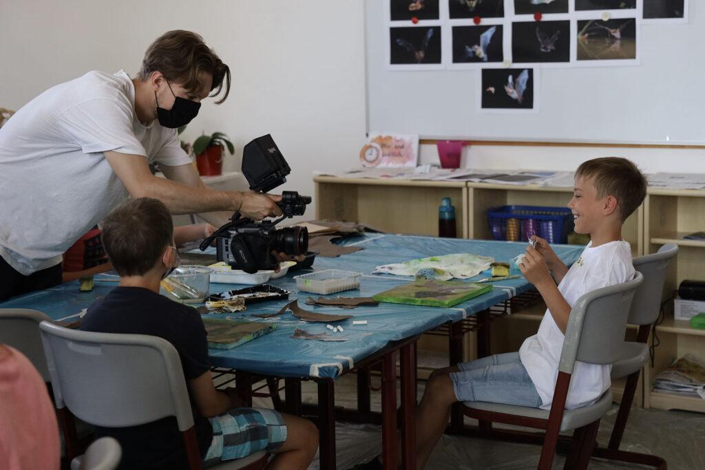 Kunstunterricht an der Grundschule Bodenmais. Ein Kind zeigt stolz sein Gemälde einer Fledermaus in die Kamera.