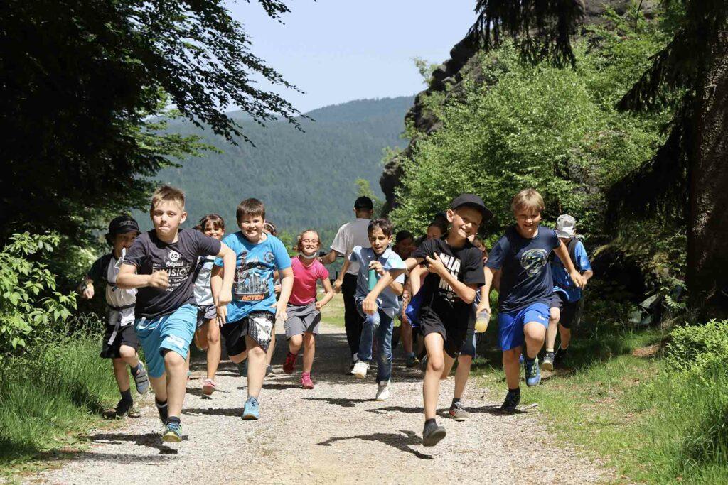 Kinder laufen den Berg hinauf. Sie sind unterwegs mit dem Gebietsbetreuer Johannes Matt.