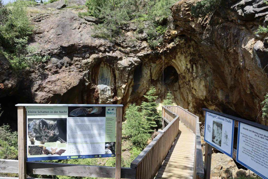 Ein Steg mit Informationstafeln führt vEin Steg mit Informationstafeln ermöglicht Einblicke in die ehemaligen Bergwerk Stollen am Silberberg.