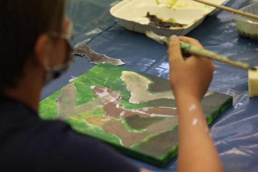 Kind der Grundschule Bodenmais malt im Kunstunterricht eine Fledermaus.