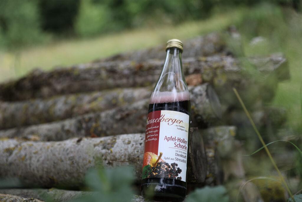 Eine Hesselberger Apfelschorle steht auf einem Holzscheiter.