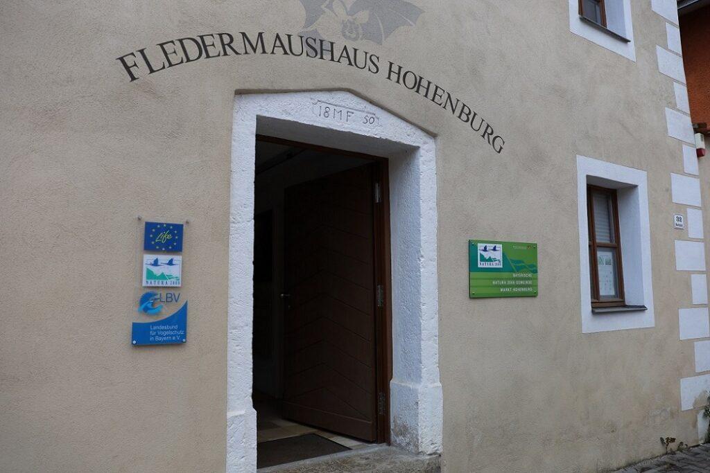 Eingangsbereich des Fledermaushauses in Hohenburg mit Schildern