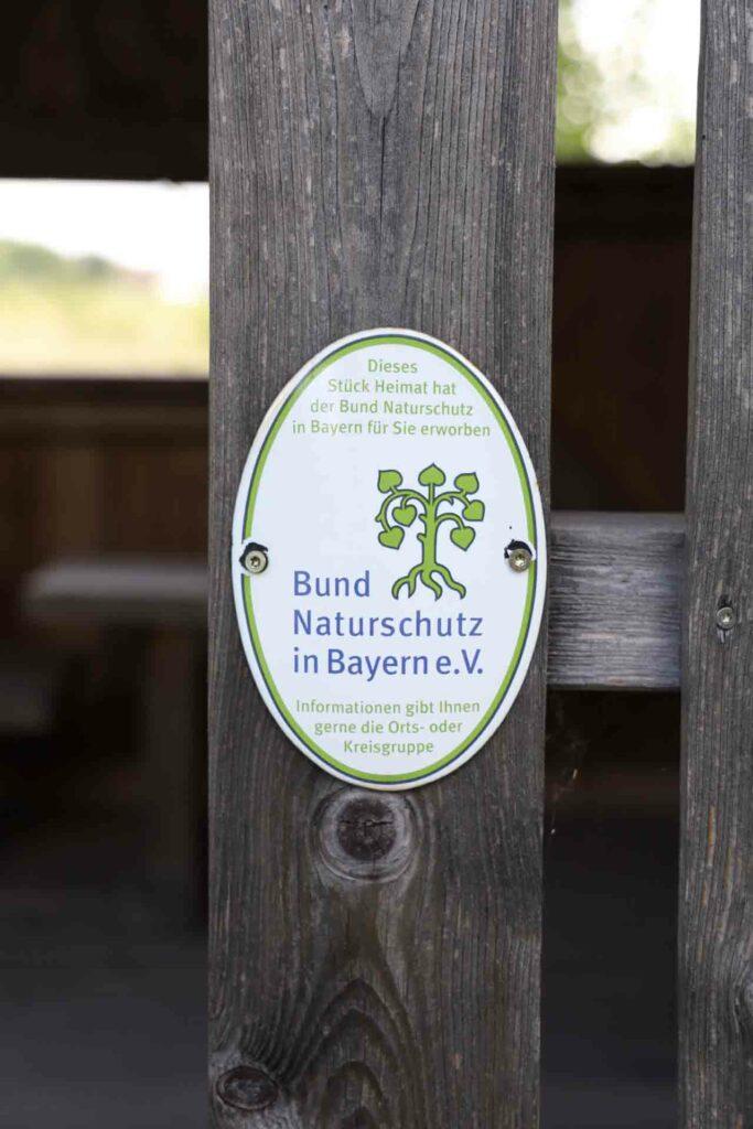 Schild des Bund Naturschutz in Bayern e. V. an dem Haussichtshäuschen.